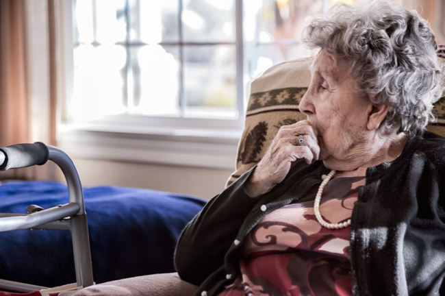 Image shows Portrait of an elderly woman sitting alone in a senior care facility.
