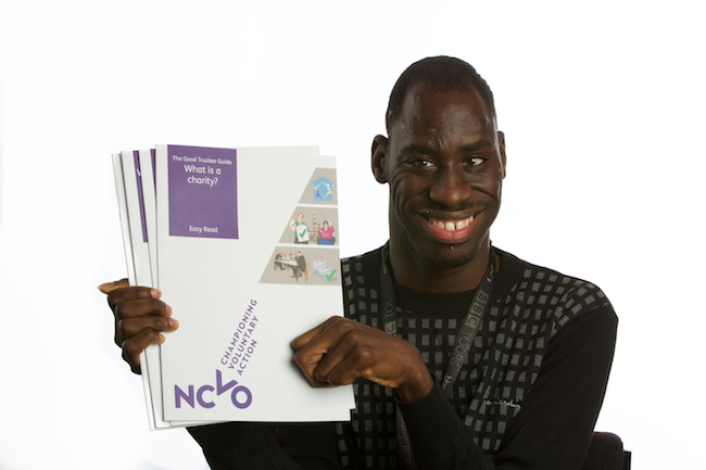 Image shows a close-up of a smiling Michael Hagan, one of The Advocacy Project trustees, holding the four easy read booklets of NCVO The Good Trustees Guide
