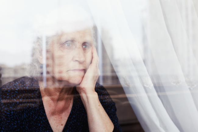 Image shows a pensive senior woman looking through a window and thinking
