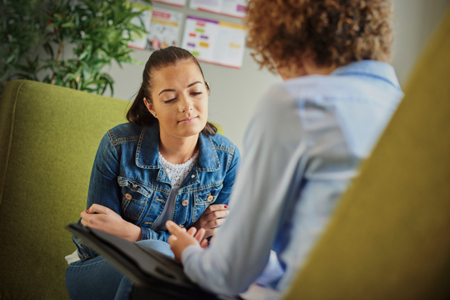 Image shows a young woman in therapy sitting opposite a counsellor and explaining her.