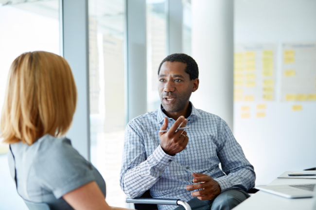 Image shows Shot of two colleagues talking together in a modern office.