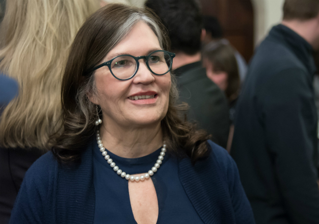 The image shows a close up of a smiling Judith Davey, Chief Executive Officer at The Advocacy Project at a public event surrounded by people.
