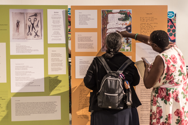 Image shows people reading poetry competition entries